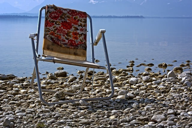 Old camping chair twisted and broken by a lake. THere are lot better RV outdoor furniture and camping chairs now adays.