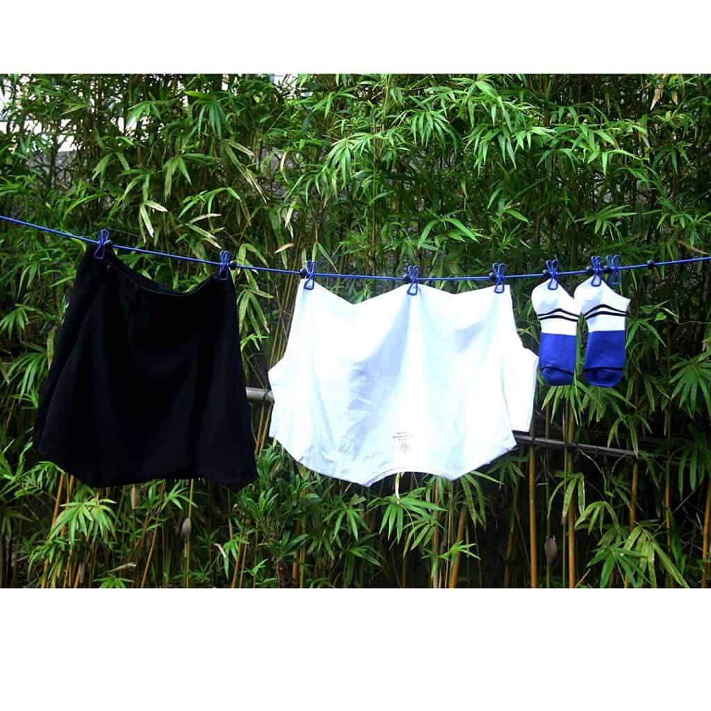 Clothesline being used to hang dry clothes and use the sun to clean them.