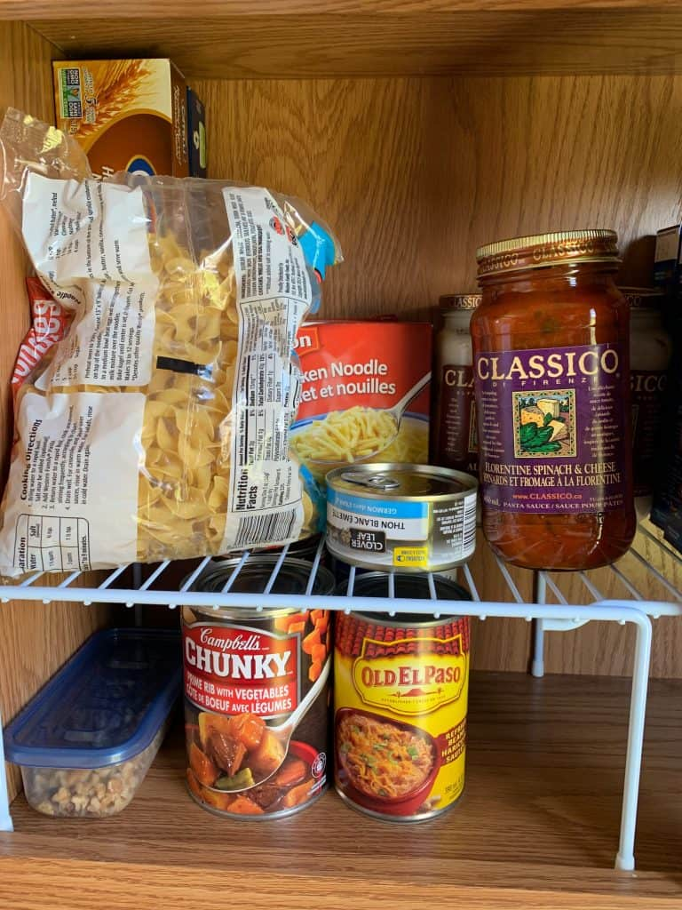 Organize RV pantry by using a wire rack shelf to provide multiple spots to place food. Just one of the good RV pantry storage ideas.