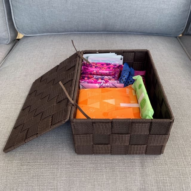 Woven plastic basket with a lid for feminine hygiene products while camping