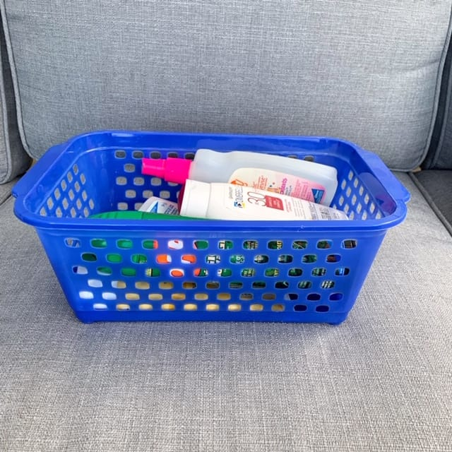 A plastic basket is a handy spot to keep the camping essentials of sunscreen and bug repellent spray