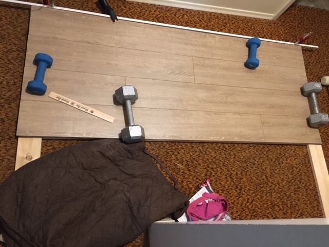 Laying the laminate flooring down and gluing it for the DIY headboard