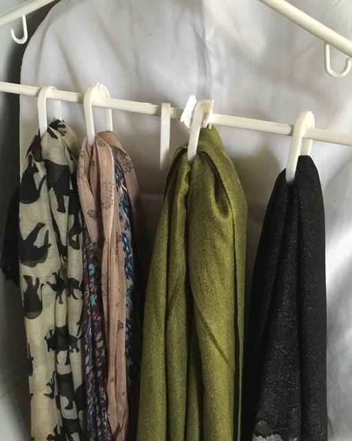 Hang scarves through plastic shower rings