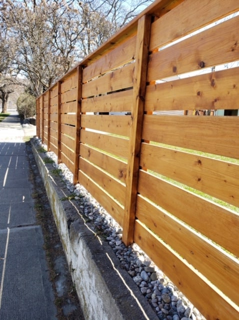 Privacy fence ideas - horizontal wood rails stained a lovely honey color. Looks so nice.