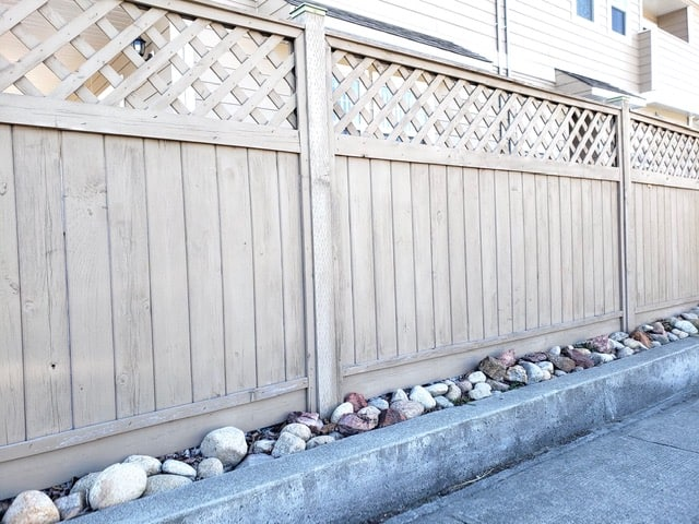 Privacy Fence Ideas - a pre-built wooden fence panel with vertical boards and a decorative lattice at the top of the fence.