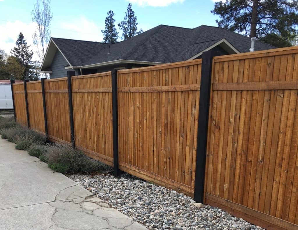 Backyard fence ideas - put a privacy fence like this wooden panel fence with the posts painted black to give it a special touch.