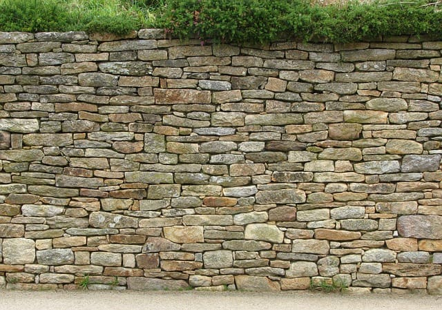 Best privacy fence ideas - a rock wall can last hundreds of years.