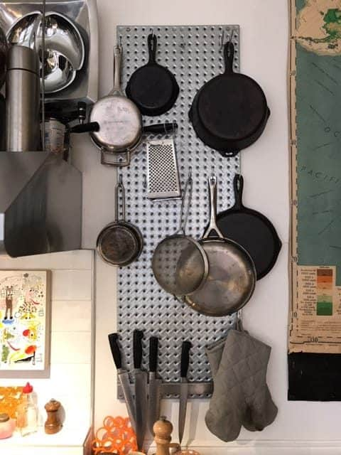 "Small kitchen organization ideas - Pegbaords and ""S"" hooks to hang pots and pans."