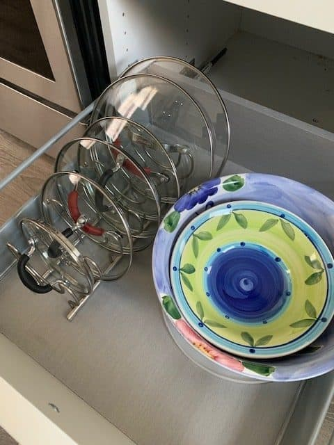 A lid organizing rack like this one can help you organize inside kitchen cabinets and large pull-out kitchen drawers.