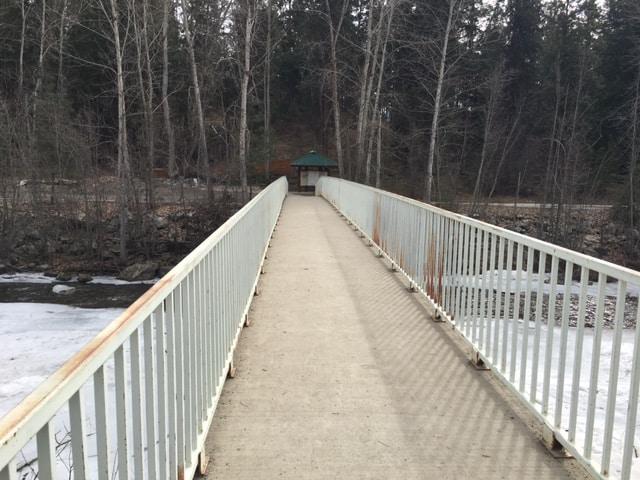 Walking over the Kokanee Bridge which goes over Mission Creek in Kelowna in the Mission Creek Regional Park.