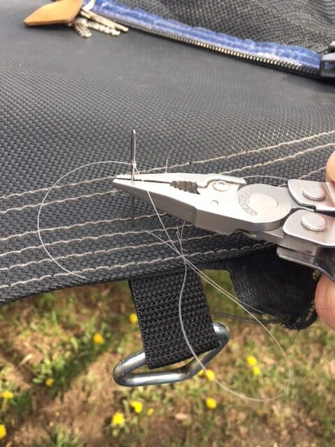 Trampoline repairs - using my Leatherman pliers to push the big sewing needle down through the trampoline mat and into the new strap