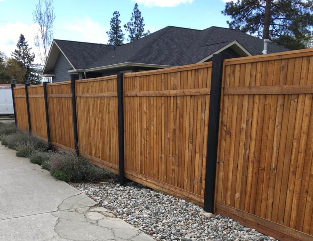 Painting your fence posts black or another color is a good way to improve the look of your wood fence