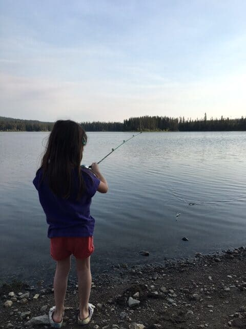 my daughter fishing from shore of Postill Lake July 2021
