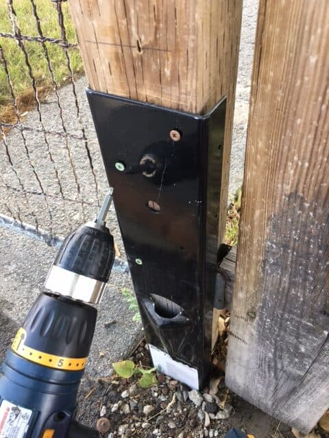 Screwing the fence mender to the fence post