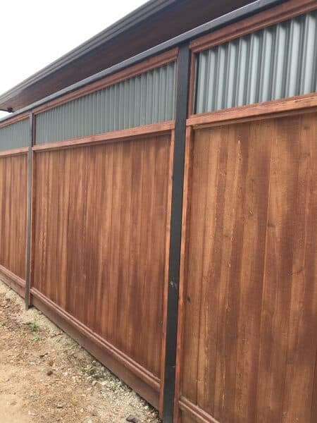 Corrugated metal panel as fence topper on a wood fence